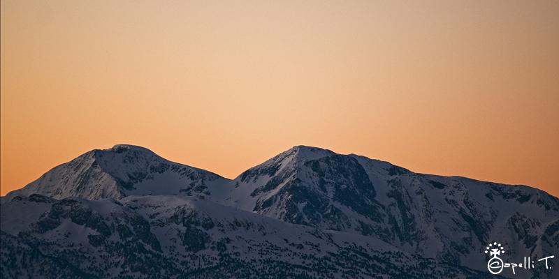 Photo d'un lever de soleil sur la croix de chamrousse avec la polution de Grenoble